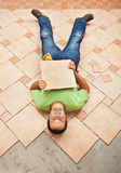 Man lying on unfinished floor tiling Stock Photo