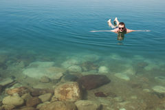 Man lying on water Dead Sea enjoying vacation .Tourism recreation, healthy lifestyle concept. Copy space Stock Photo