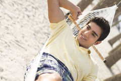 Man lyning in a hammock. An attractive young man lying in a hammock on the beach Royalty Free Stock Photo