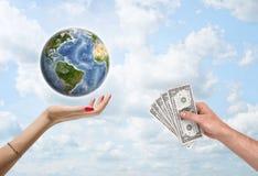 Man& x27; mão de s que dá notas de dólar à fêmea, que apoia a terra do planeta fotografia de stock royalty free