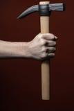 Man& x27; mão de s que guarda o martelo no fundo vermelho imagens de stock royalty free