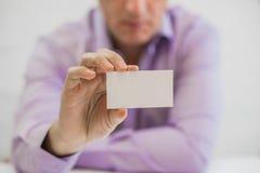 Man& x27; mão de s que mostra o cartão - o close up disparou no fundo branco Fotos de Stock Royalty Free