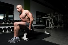 Man On Machine Exercising Quadriceps And Glutes. Strong Man In The Gym And Exercising Quadriceps And Glutes On Machine - Muscular Athletic Bodybuilder Fitness Royalty Free Stock Photography