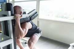 Man On Machine Exercising Quadriceps And Glutes. Strong Man In The Gym And Exercising Quadriceps And Glutes On Machine - Muscular Athletic Bodybuilder Fitness Royalty Free Stock Photos