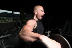 Man On Machine Exercising Quadriceps And Glutes. Strong Man In The Gym And Exercising Quadriceps And Glutes On Machine - Muscular Athletic Bodybuilder Fitness Stock Image