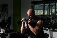 Man On Machine Exercising Quadriceps And Glutes. Strong Man In The Gym And Exercising Quadriceps And Glutes On Machine - Muscular Athletic Bodybuilder Fitness Stock Photo