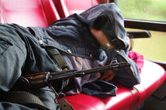 Soldier holds a machine gun between his legs while he is having a siesta an a journey coach Stock Image