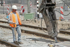 Man and Machine at work. Delft, The Netherlands - June 24: Man working in new central station construction site, on June 24 in Delft, The Netherlands. They are Royalty Free Stock Images