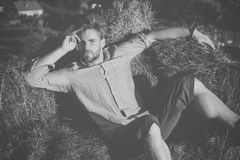 Man or macho in shirt and shorts lying in hay Stock Photos