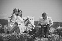 Man or macho typing on vintage typewriter on hay. Happy women or girls reading books on bench. Education and knowledge Royalty Free Stock Photography