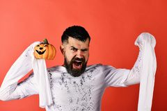 Man with mad face expression on red background. Halloween character. In white long sleeved ghost costume. Halloween and international celebrations concept. Guy royalty free stock image