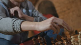 The man made a move as a bishop during playing chess. The man made a move as a bishop. The man`s hand takes the figure of the horse from the chessboard. Young stock video