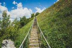 Man-made staircase upstairs to the hill with green grass, travel and tourism concept Royalty Free Stock Photos