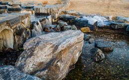 Man made waterfall emptying into a rocky stream. With large boulders on either side in a public park on a sunny afternoon in February Stock Image