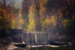 Man Made Waterfall in the Forest. Autumn colors in the forest and a stone man made waterfall touched by the sunlight stock photography
