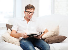 Man with magazine at home Royalty Free Stock Photography