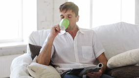 Man with magazine at home Stock Image