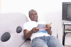 Man with Magazine on sofa Royalty Free Stock Photography