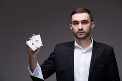 Man magician with two playing cards in his hand over grey background stock image