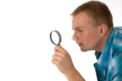 Man with magnifier. Young man looks through a magnifying glass Royalty Free Stock Images