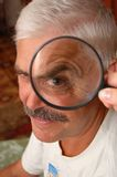 Man and magnifier. Mature man and magnifier on his eye Stock Images