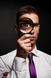 Man with magnifier. On dark background stock images