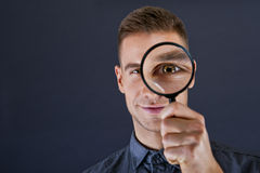 Man with magnifier. On dark background stock image