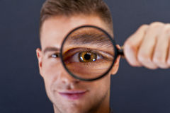 Man with magnifier on dark background Royalty Free Stock Images
