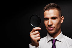 Man with magnifier on dark background Stock Photography