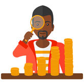 Man with magnifier and golden coins Royalty Free Stock Image