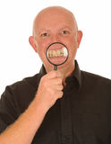 Man with magnifier on teeth. Man holding magnifier in front of open mouth showing enlarged image of teeth all on a white background stock photos
