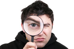 Man with magnifying glass. Man looking at camera through magnifying glass Royalty Free Stock Photo