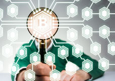 Man with magnifying glass, bitcoin Stock Photo