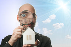 Man with a magnifying glass and paper house. Real estate concept on a blue background Stock Image