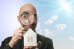 Man with a magnifying glass and paper house. Real estate concept on a blue background Stock Photo