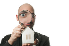 Man with a magnifying glass and paper house. Real estate concept. Isolated on a white background Royalty Free Stock Photo