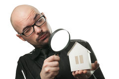 Man with a magnifying glass and paper house. Real estate concept. Isolated on a white background Stock Image