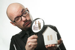 Man with a magnifying glass and paper house. Real estate concept on a white background Royalty Free Stock Image