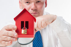 Man with a magnifying glass and paper house Royalty Free Stock Images