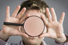 Man with magnifying glass. Showing teeth Royalty Free Stock Photos
