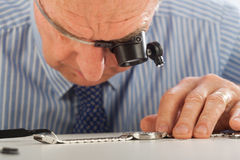 Man with Magnifying Glasses Fixing Watch Royalty Free Stock Images