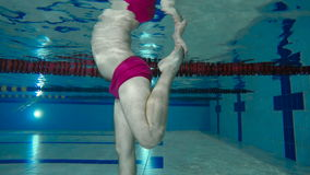 The man make sport exercises with leg underwater in swimming pool. Underwater shooting. Camera focuses on man`s body. He standing in the swimming pool and stock video footage