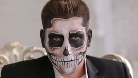 Man with make-up skeleton sitting in old grey chair. Halloween or horror theme. Businessman with make-up skeleton sitting in the old grey chair, and creepy stock video footage