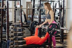 Man makes a bench press, he is insured by a girl coach, a sports gym theme stock images