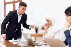 A man makes a claim to a woman wearing a hijab. royalty free stock image