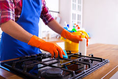 Man makes cleaning the kitchen. Young man washes an oven. Cleani Stock Photos