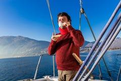 Man makes a coffee break on sailboat Stock Photo