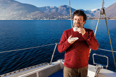 Man makes a coffee break on sailboat Stock Image