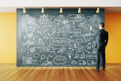 Man makes concept strategy plan on blackboard in the roo Stock Photo