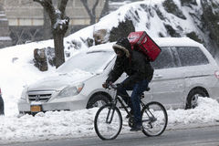 Man makes delivery on bike in snow storm Royalty Free Stock Images